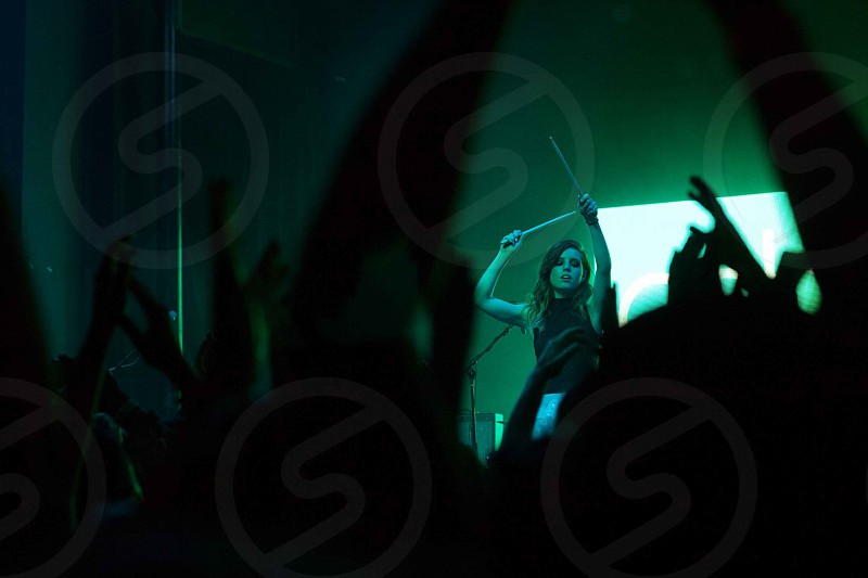 silhouetted people dancing at concert in front of woman playing drums onstage photo