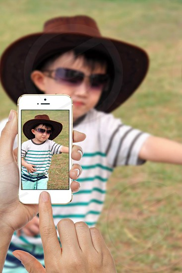 person taking photo of boy wearing brown cowboy hat sunglasses and white green and black stripe shirt using gold iphone 5s during daytime photo