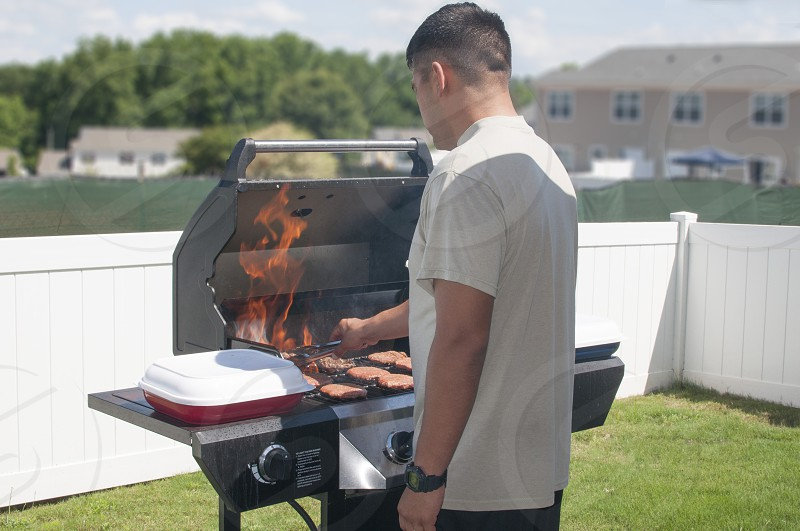 man in white button up t-shirt standing in front of outdoor grill on backyard during daytime photo