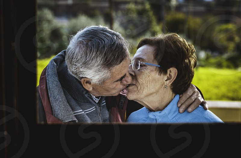 Elderly couple kissing and showing their love behind the window with the background field photo