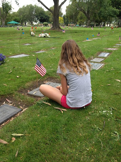 girl sitting by grave stone with american flag post photo