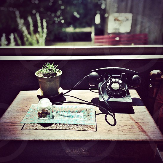 shallow focus photography of black rotary dial desk phone on top of table photo