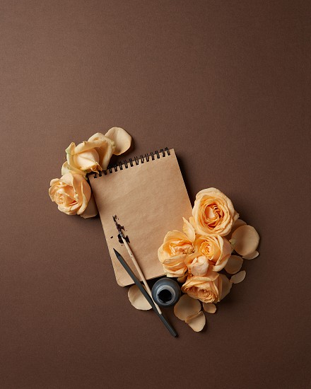 Diary or notebook with pen and ink for your notes. Notebook with brown pages with orange roses represented on brown background. photo