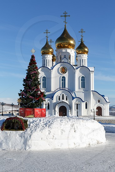 PETROPAVLOVSK CITY KAMCHATKA PENINSULA RUSSIA - JAN 6 2018: Holy Trinity Orthodox Cathedral of Petropavlovsk Kamchatka Diocese of Russian Orthodox Church and Christmas tree in front of building photo