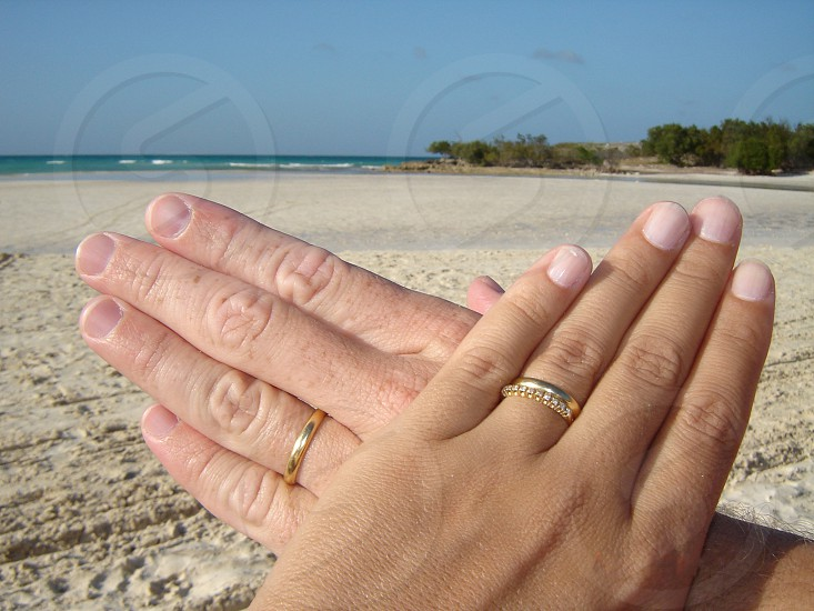 hands with gold rings on the beach in Cuba  photo