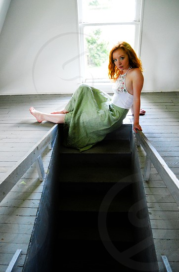 woman wearing white halter shirt and green skirt sitting on attic ladder top during daytime photo