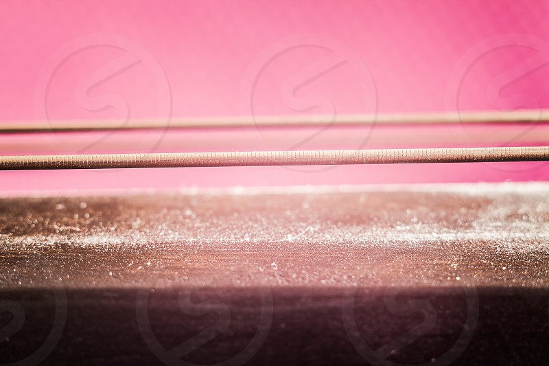 Details of a cello neck with strings on purple background. photo