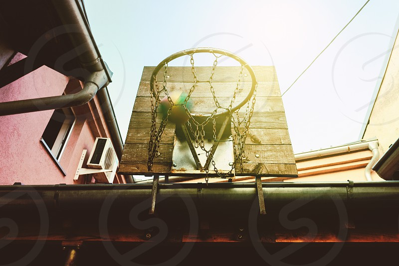 Details of an old  backyard basketball hoop hanged on roof of a house day scene. photo