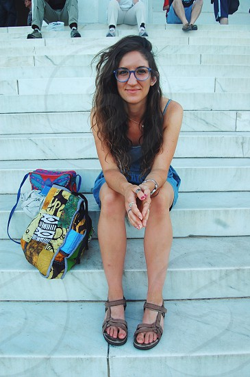 woman wearing a blue dress and eyeglasses sitting on outdoor steps photo