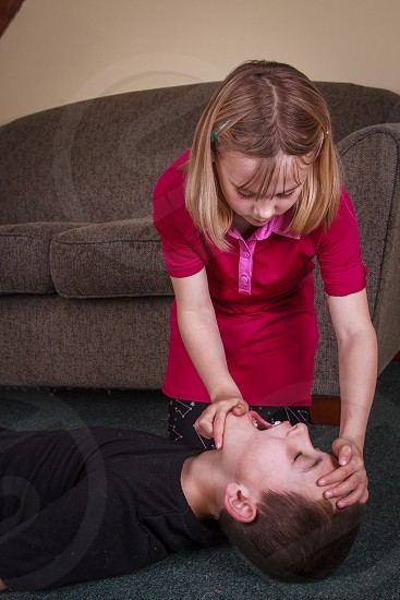 Girl opening a boy's mouth and tipping his head back to check his airways. photo