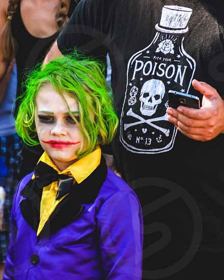 A portrait image of a young boy in costume of the joker from the Batman the dark Knight movie at a comic con event Halloween facepaint photo