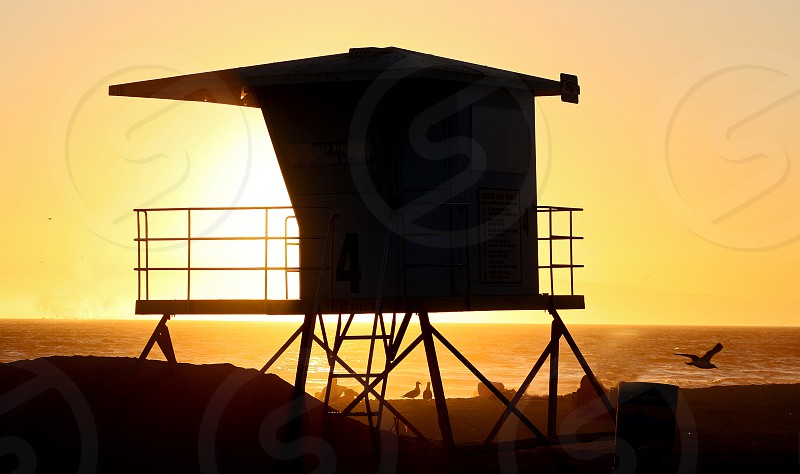 Lifeguard in silhouette hut at sunset photo