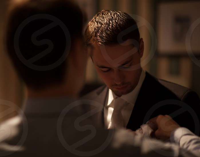 Groomsman fixing white boutonniere on groom's suit. Preparation before wedding ceremony photo