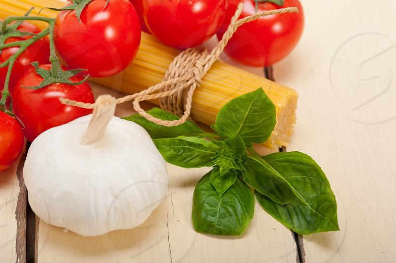 Italian basic pasta fresh ingredients cherry tomatoes garlic and basil photo