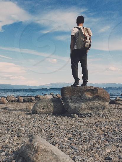 man wearing white shirt with brown rucksack bag standing on gray rock photo