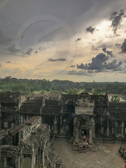 Outdoor day colour vertical portrait Angkor Wat Temple complex Cambodia Asia Asian east eastern orient spiritual holy religious religion Buddhism Buddhist ancient crumbling stone carved stonework masonry elaborate intricate columns travel traveller travelling tourism tourist wanderlust adventure explore exploration cloud cloudy atmospheric sky lush green tropical architecture rain raindrops drops droplets storm stormy moody sunset photo