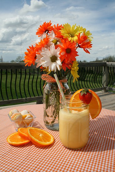 Orange smoothie garnished with a strawberry and orange slice with a mason jar of daisies and white chocolate covered cake balls on an orange gingham tablecloth photo
