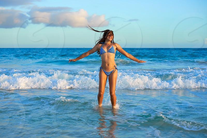 Latin beautiful bikini girl happy jumping in Caribbean beach sunset photo