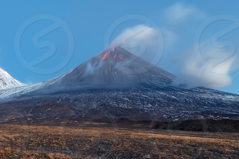 Volcanic landscape of Kamchatka: eruption Klyuchevskoy Volcano lava flows on slope of volcano; plume of gas steam ash from crater. Kamchatka Peninsula Russia Klyuchevskaya Group of Volcanoes. photo