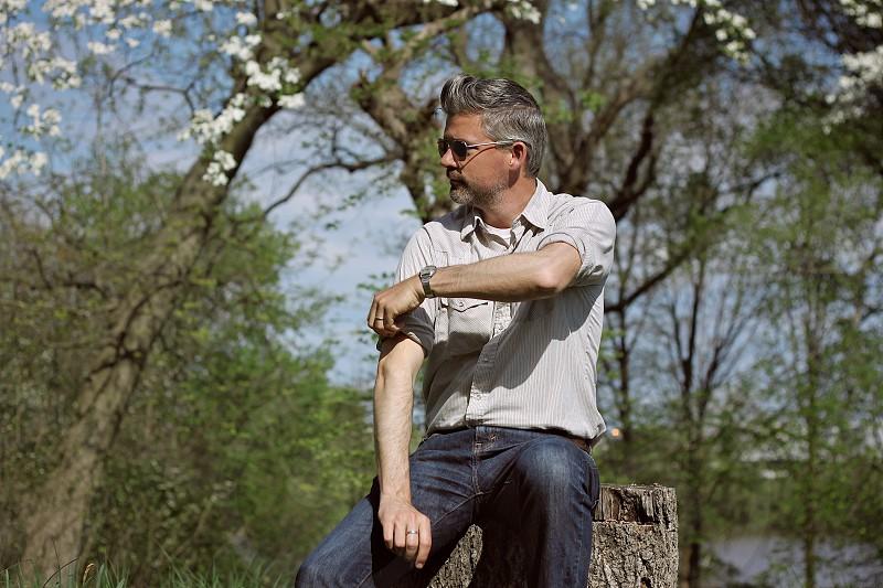 portrait man field spring thinking flowers nature tree stump sleeve roll sunglasses photo