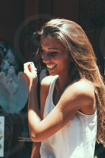 woman in white tank top smiling photo