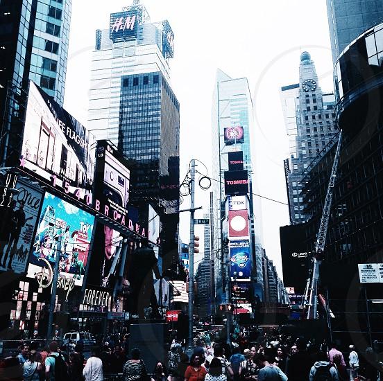 people walking beside buildings in city photo