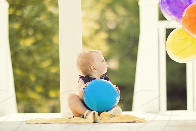 baby holding blue balloon photo