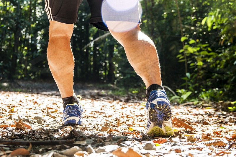 Low angle view of running legs of an adult male in forest park trail photo