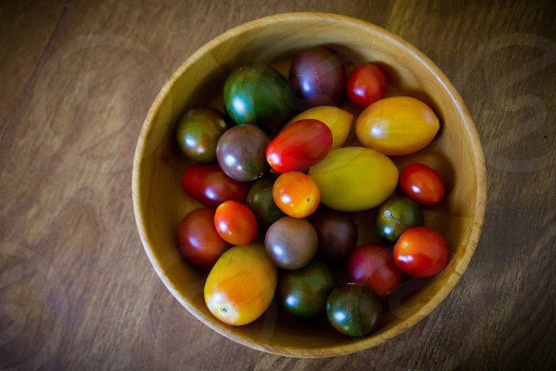 colored oval fruits in brown round bowl on the table photo