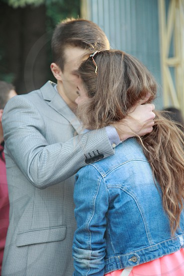 man in gray blazer hugging woman in blue denim crop jacket during daytime photo