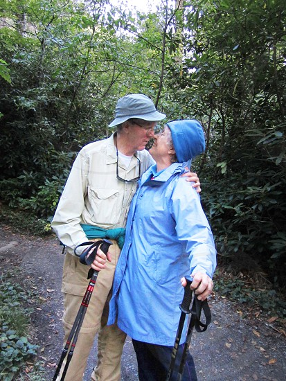 Older Elderly Couple celebrating end of a mountain hike with a kiss. photo