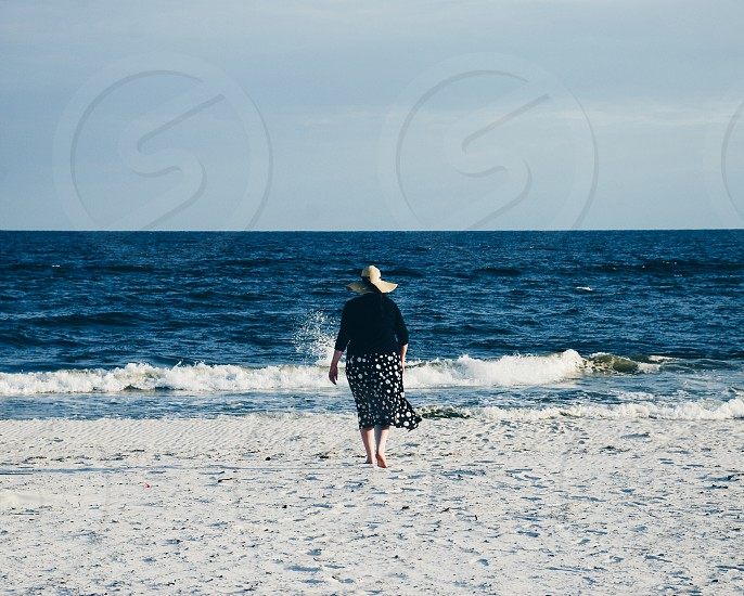 woman walking alone towards the waves on a beach. photo