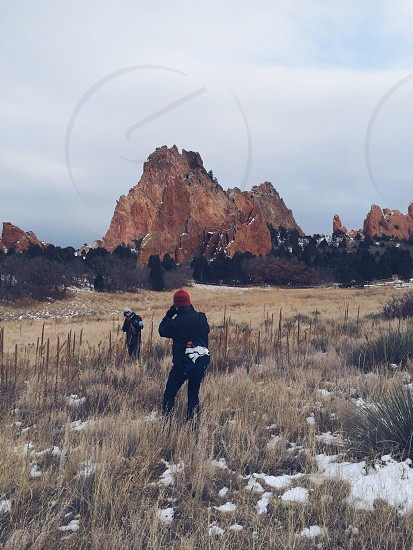 person in red beanie taking picture of person in white beanie with brown mountain background photo