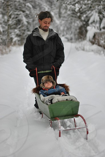 man pushing sled with baby inside photo