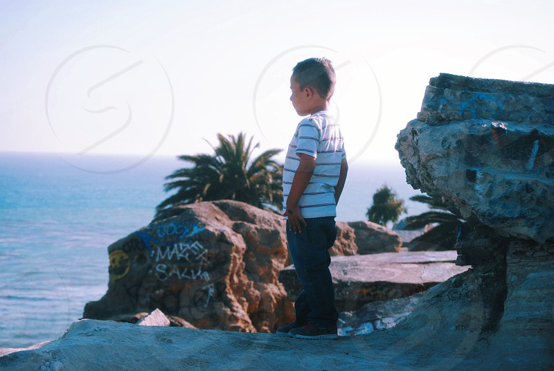 boy in white and black striped t shirt and blue pants photo