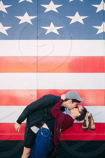 man and woman kissing in front of american flag design structure photo