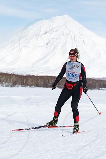 PETROPAVLOVSK CITY KAMCHATKA PENINSULA RUSSIA - FEB 10 2018: Sportswoman skier running along the winter ski track on background of Koryak Volcano. All-Russia mass ski race - Ski Track of Russia. photo
