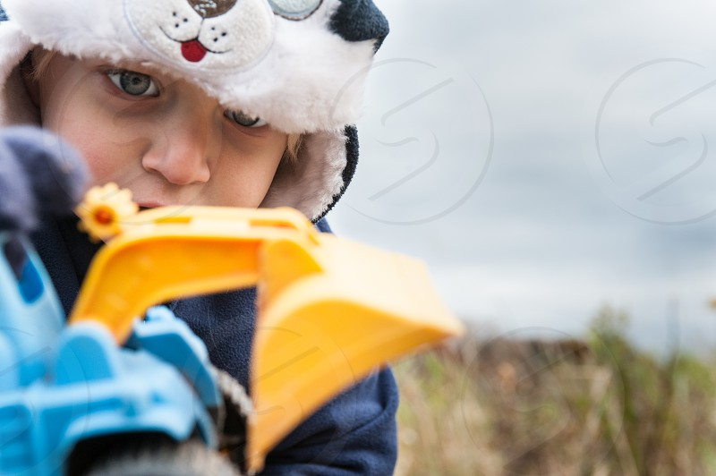 boy child youth play imagine imagination hat fall winter cold tractor sandbox truck construction build outside gloves blue yellow scoop bulldozer loader clouds sky photo