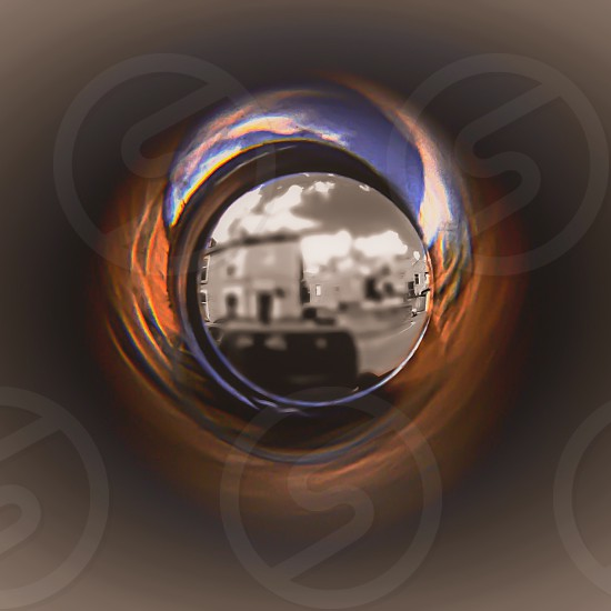 Looking through eye piece in door... Color being fade and and caught in a vortex... Blue sky's..... Orange brick house orange bricks photo
