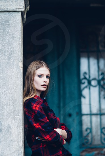 woman in red plaid shirt leaning against wall photo