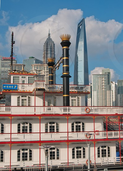 shanghai pudong view from puxi new bund with steam boat on huangpu river on foreground photo