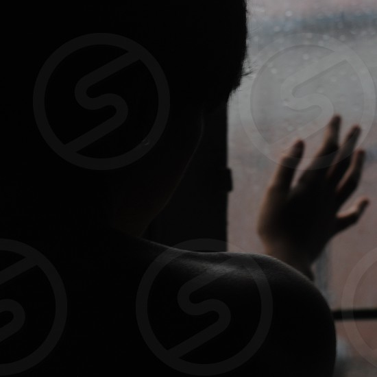 person touching glass window photo