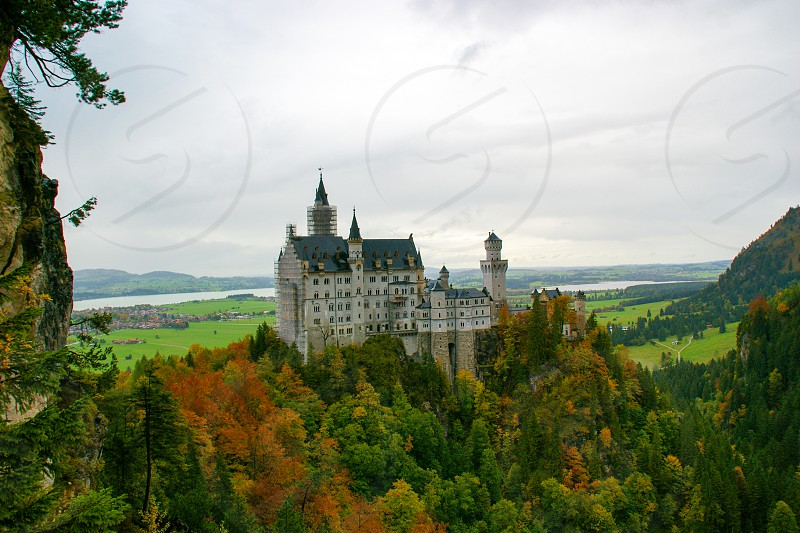 Füssen Bavaria/Germany ; 04/27/2018: Hohenschwangau Castle surrounded by a colorful autumnal forest and a lake photo