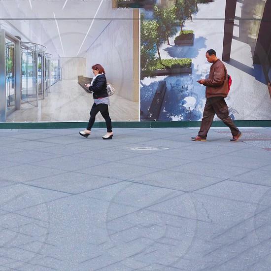 man and woman walking near wall photo