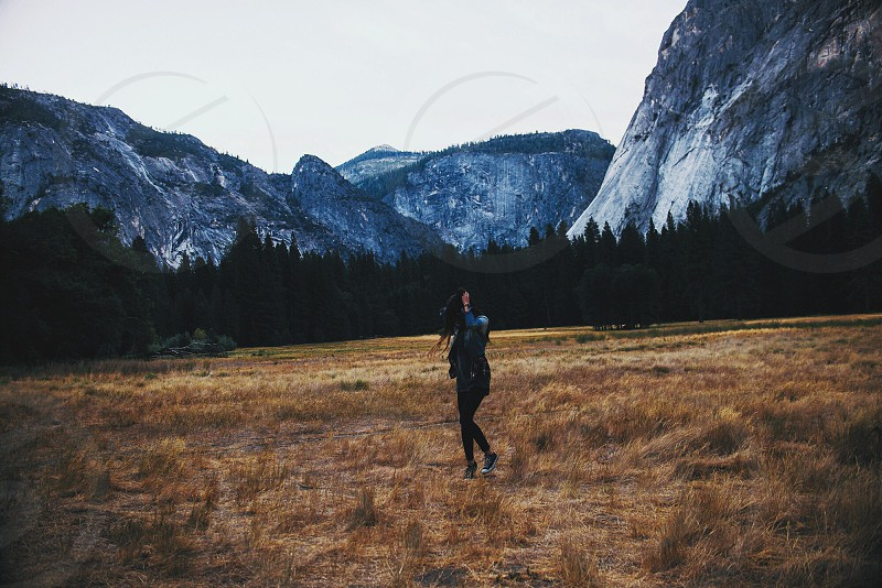 woman in black pants near hill photo