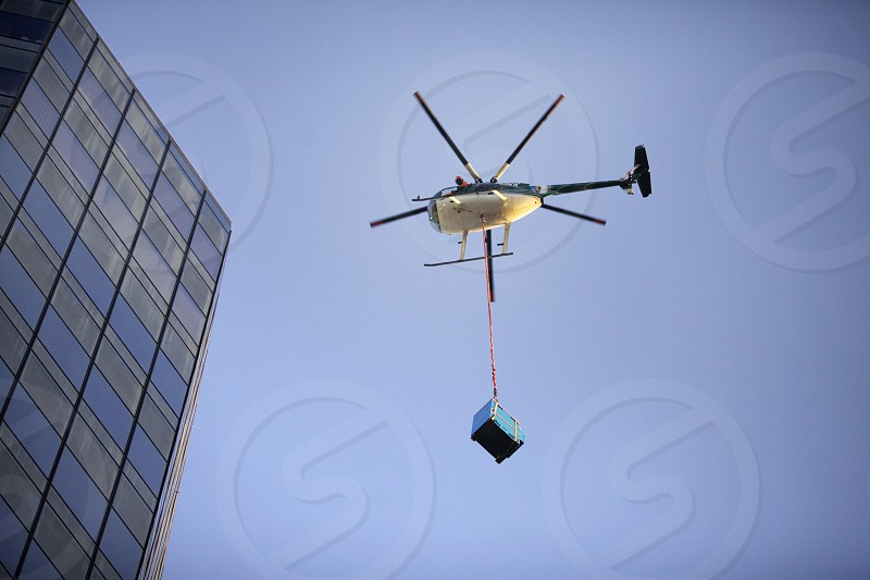 Helicopter lifting a payload onto a building. chopper sky city high-rise blades photo