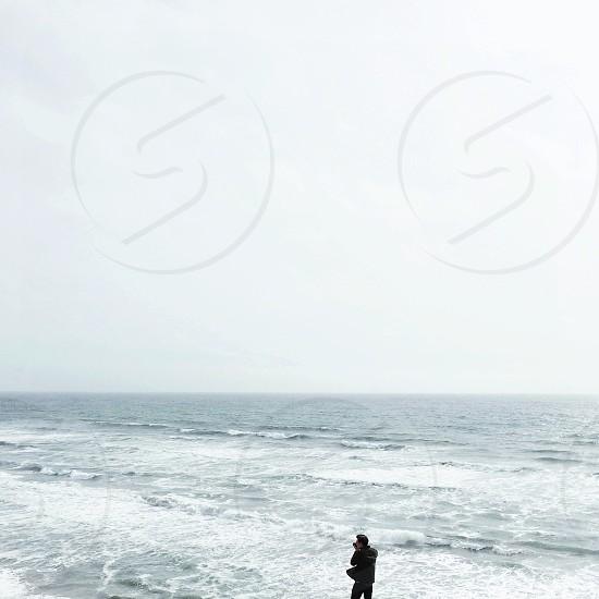 man in black jacket walking on beach photo