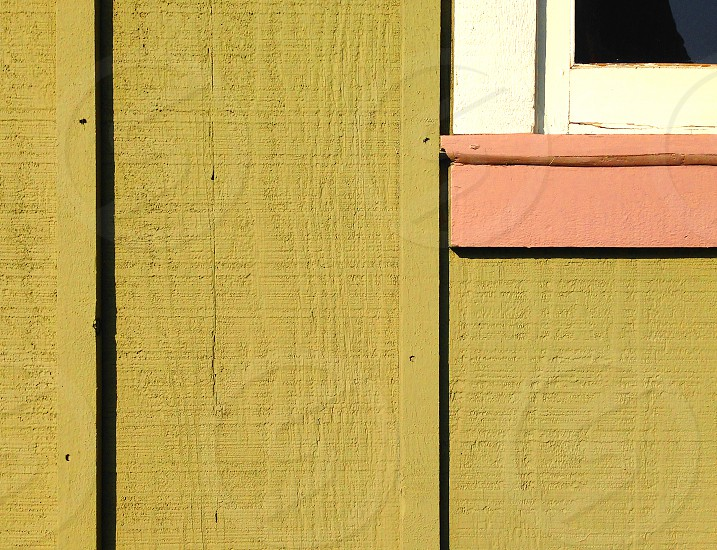 Abstract detail of a corner of a wood frame window and sill on a lime green house. photo