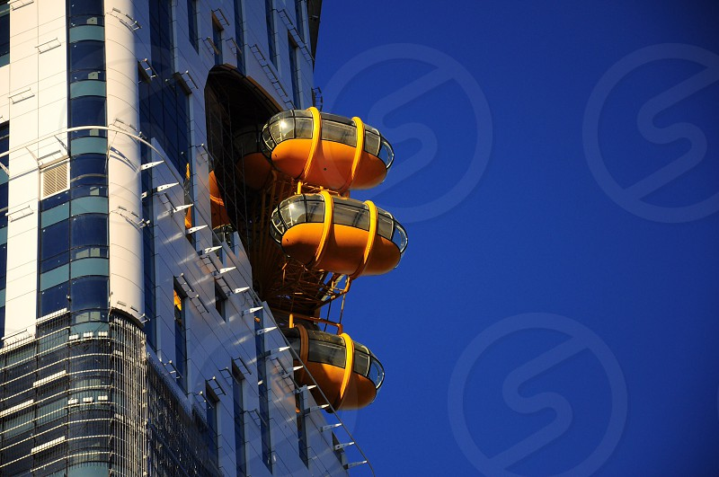 yellow oval shaped building rooftop rides photo