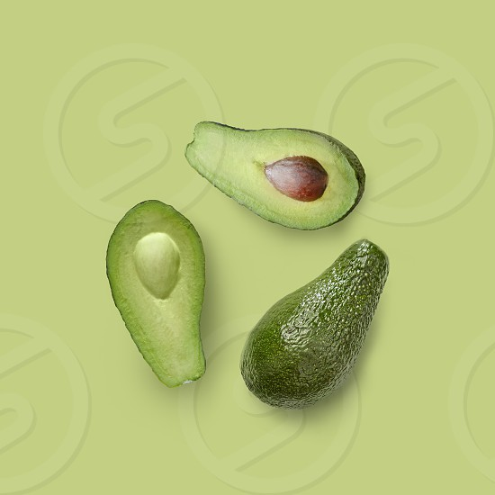 halves and whole green fresh avocado on a green background flat lay isolated photo